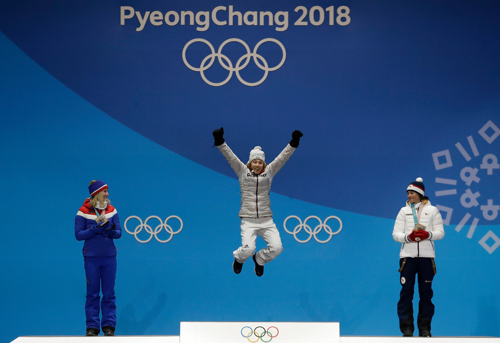 . Women\'s 7.5km biathlon sprint silver medalist Marte Olsbu, left, of Norway, and bronze medalist Veronika Vitkova, right, of the Czech Republic applaud as gold medalist Laura Dahlmeier, of Germany, celebrates during their medals ceremony at the 2018 Winter Olympics in Pyeongchang, South Korea, Sunday, Feb. 11, 2018. (AP Photo/Morry Gash)