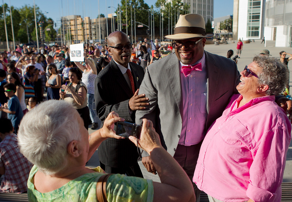 . From right, Judy Rickard and Rick Callender, V.P. of the California Hawaii NAACP, get their photo taken by Rickard\'s partner Karin Bogliolo, at a San Jose City Hall rally to celebrate the U.S. Supreme Court decision on DOMA and Proposition 8, in San Jose, Calif. on Wednesday, June 26, 2013. (LiPo Ching/Bay Area News Group)
