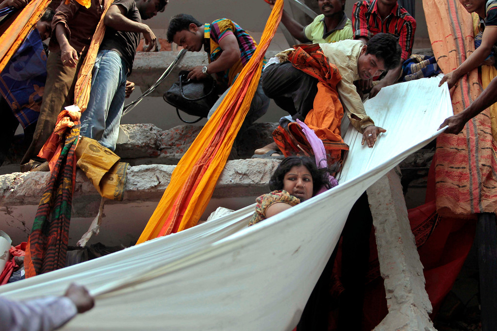 . Rescue workers use pieces of clothes to bring down a survivor after an eight-story building housing several garment factories collapsed in Savar, near Dhaka, Bangladesh, Wednesday, April 24, 2013.  (AP Photo/ A.M. Ahad)