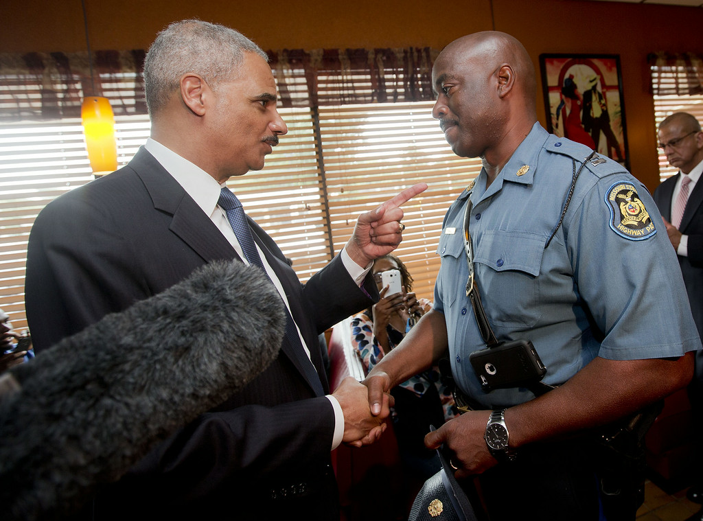 ". FLORRISSANT, MO - AUGUST 20:  U.S. Attorney General Eric Holder (L) talks with Capt. Ron Johnson, right, of the Missouri State Highway Patrol at Drake\'s Place Restaurant,August 20, 2014 in Florrissant, Missouri. Holder is traveling to Ferguson, Mo., to oversea the federal government\'s investigation into the shooting of 18-year-old Michael Brown by a police officer on Aug. 9th. Holder promised a ""fair and thorough\"" investigation into the fatal shooting of a young blackman, Michael Brown, who was unarmed when a white police officer shot him multiple times. (Photo by Pablo Martinez Monsivais-Pool/Getty Images)"