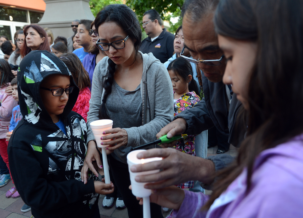. 0508_NWS_IDB_L-SAMMY-01-JCM (Jennifer Cappuccio Maher/Staff Photographer) Victoria Rivera, of Chino, center, helps her son Ethyn, 8, with his candle as friends and family attend a candlelight vigil for Samantha Padilla Tuesday, May 7, 2013, near the corner of Euclid Ave and Schaefer Ave in Chino. Padilla passed away April 30 from injuries sustained during a car accident.
