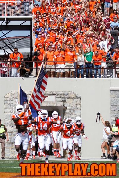 Isaiah Ford (1) carries the American flag into Lane Stadium during Enter Sandman. (Mark Umansky/Thekeyplay.com)