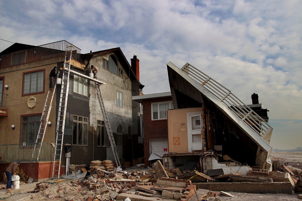 . Men repair a home damaged by Superstorm Sandy next to a one that is almost collapsed on the Rockaway Peninsula in New York, Thursday, Nov. 29, 2012.  Sandy damaged or destroyed  305,000 housing units in New York.  (AP Photo/Seth Wenig)