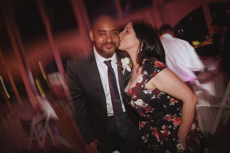 A groomsman smiles as his wife kisses him on the cheek.