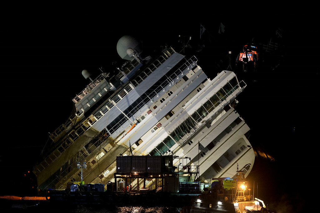 . The Costa Concordia ship lies on its side on the Tuscan Island of Giglio, Italy, Monday, Sept. 16, 2013. Using a vast system of steel cables and pulleys, maritime engineers on Monday gingerly winched the massive hull of the Costa Concordia off the reef where the cruise ship capsized near an Italian island in January 2012. But progress in pulling the heavily listing luxury liner to an upright position was going much slower than expected. Delays meant the delicate operation � originally scheduled from dawn to dusk Monday � was not expected to be completed before Tuesday morning. (AP Photo/Andrew Medichini)