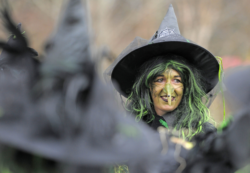 . A woman costumed as a witch smiles during a procession in Schierke, central Germany, Tuesday, April 30, 2013. Hundreds of costumed devils and witches meet to celebrate Walpurgis Night, a traditional religious holiday of pre-Christian origins. The event is named after St. Walburga, an English nun who helped convert the Germans to Christianity in the 8th century. (AP Photo/Jens Meyer)