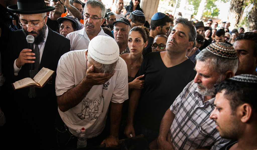 """. People mourn during the funeral of Dror Khenin at a cemetary on July 16, 2014 in Yahud Monoson, Israel. Yesterday Khenin was the first Israeli to be killed by a Hamas mortar as he offered food to Israeli soldiers working near the Erez border crossing between Israel and Gaza. As Operation \""""Decisive Edge\"""" enters its ninth day, over 200 Palestinians have been killed in Israeli missile strikes.  (Photo by Andrew Burton/Getty Images)"""