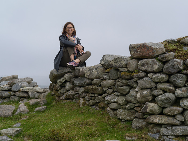 Woman sitting on stacked rocks, Achill Island, County Mayo, Ireland