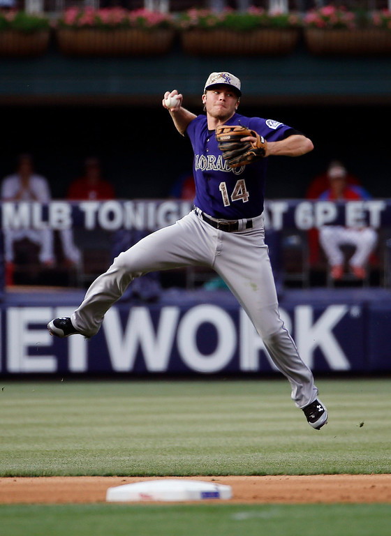. Colorado Rockies second baseman Josh Rutledge leaps to make a throw to first base on a single by Philadelphia Phillies\' Chase Utley during the fourth inning of a baseball game, Monday, May 26, 2014, in Philadelphia. (AP Photo/Matt Slocum)