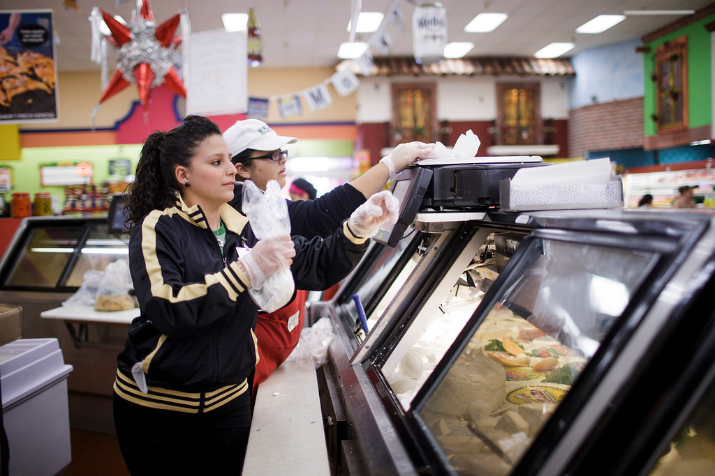 . Mi Pueblo Food Center employees Daniela Dominguez, left, and Gabriela Cachu, center, work in the deli section on July 24, 2013 in San Jose. The Bay Area supermarket chain filed for Chapter 11 bankruptcy protection Monday, citing a dispute with its primary lender, Wells Fargo. (Dai Sugano/Bay Area News Group)
