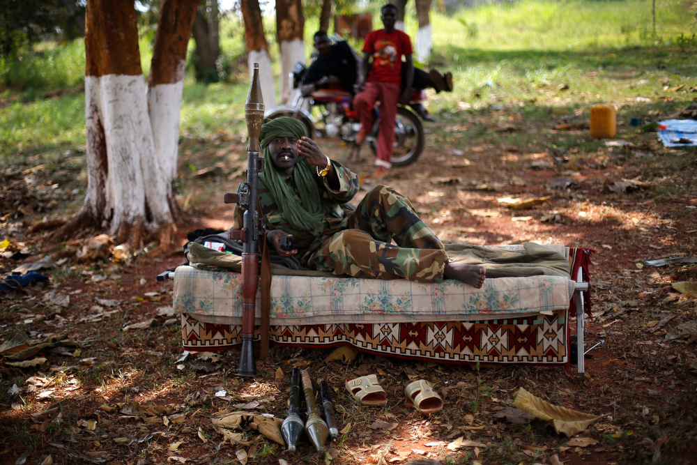 . A Muslim Seleka militiaman motions to the photographer to stop taking pictures as he rests on a cot in the Seleka controlled town of Mbaiki, some 120kms (75 miles) south west of Bangui, Central African Republic, Sunday Jan. 26, 2014. A local commander of the Muslim Seleka blamed Christian anti Balaka militias for sending the country into chaos and vowed reprisals if the newly appointed interim government would not put an end to Muslim killings in the country. (AP Photo/Jerome Delay)