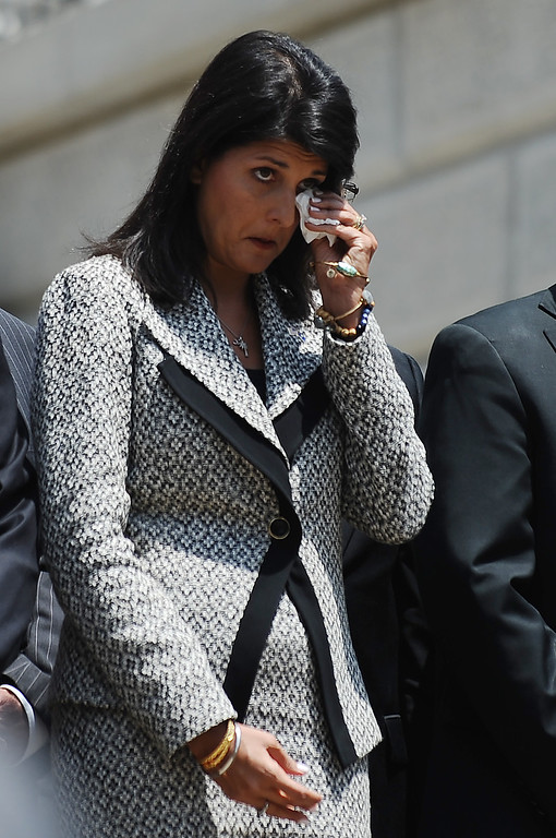 . Gov. Nikki Haley wipes her face as the body of Sen. Clementa Pinckney arrives at the South Carolina Statehouse, Wednesday, June 24, 2015, in Columbia, S.C. Pinckney\'s open coffin was put on display under the dome where he served the state for nearly 20 years. Pinckney was one of those killed in a mass shooting at the Emanuel AME Church in Charleston. (AP Photo/Rainier Ehrhardt)