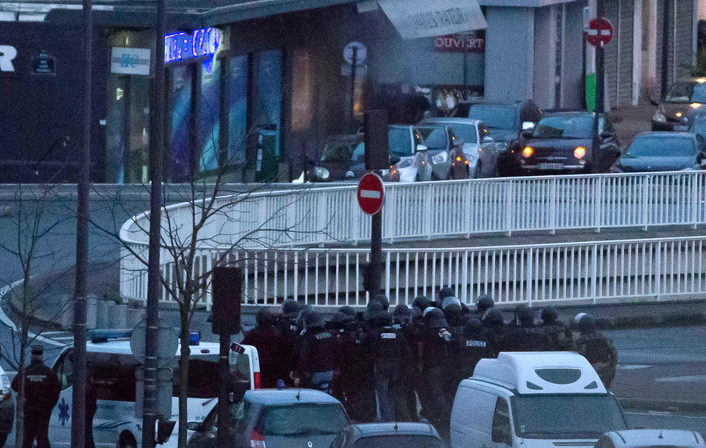 . Smoke emanates from the entrance to a kosher market as security forces prepare to end a hostage situation, Paris, Friday, Jan. 9, 2015. Explosions and gunshots were heard as police forces stormed a kosher grocery in Paris where a gunman was holding at least five people hostage. (AP Photo/Michel Euler)