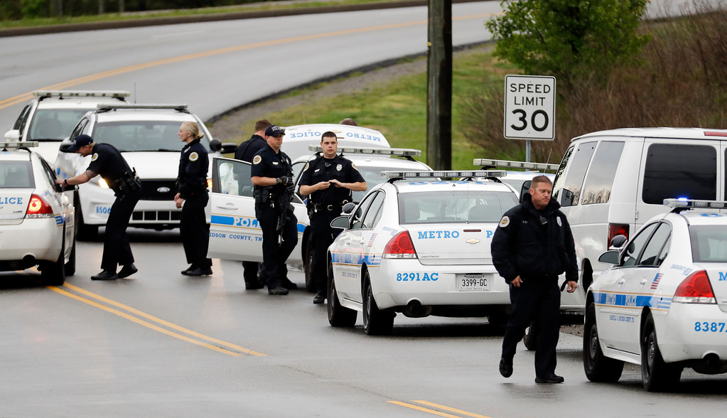 . Nashville police officers gather alongside a wooded area as they search for a shooting suspect near a Waffle House restaurant Sunday, April 22, 2018, in Nashville, Tenn. At least four people died after a gunman opened fire at the restaurant early Sunday. (AP Photo/Mark Humphrey)