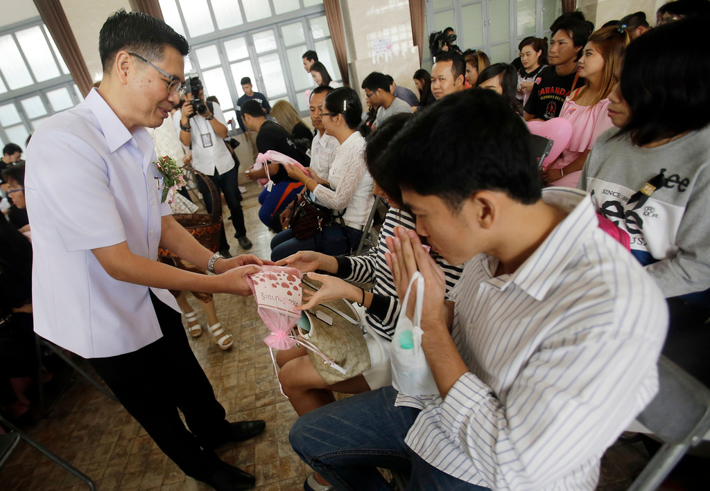 ". Thai officer give the pills are prenatal vitamins containing folic acid and iron to couples wait to sign their marriage certificates in Bangkok, Thailand, Tuesday, Feb. 14, 2017. Just in time for Valentine\'s Day, the Thai government is distributing pills it calls ""very magical vitamins\"" to prospective mothers boost the country\'s falling birthrate. The pills are prenatal vitamins containing folic acid and iron and being handed out to women between the ages of 20-34. (AP Photo/Sakchai Lalit)"