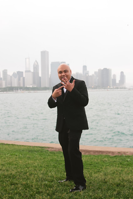 the groom shows off his wedding band in front of the chicago skyline