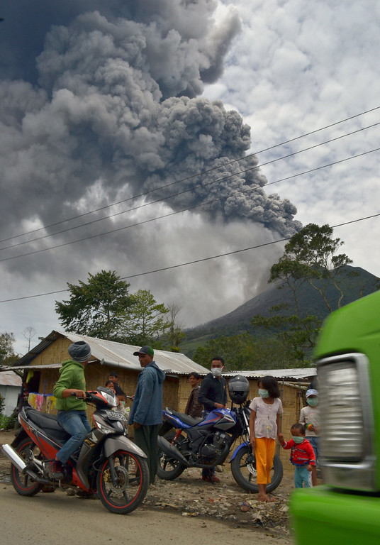 . Residents leave the district of Karo as an ash cloud rises during a fresh eruption of the Mount Sinabung volcano on September 17, 2013. Thousands of villagers fled after Mount Sinabung\'s series of volcanic eruptions on Indonesia\'s Sumatra island, spewing rocks and red-hot ash onto surrounding villages, officials said.   SUTANTA ADITYA/AFP/Getty Images