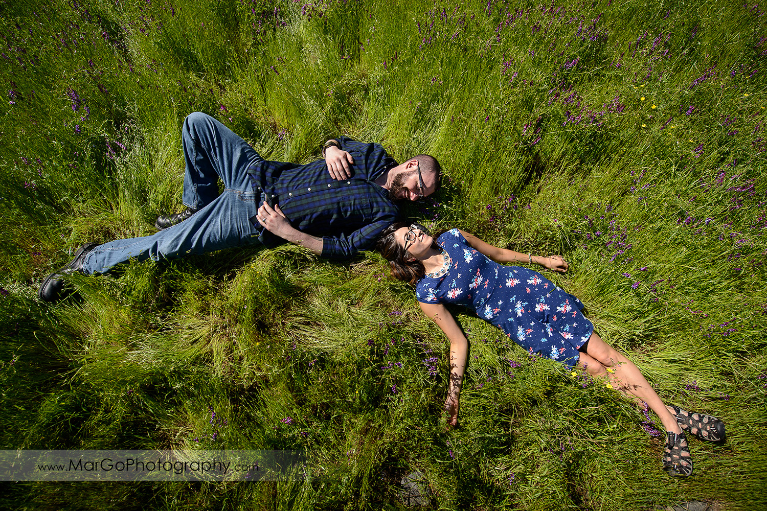 woman in blue dress and man in blue shirt lying on the grass during engagement session at Sunol Regional Wilderness