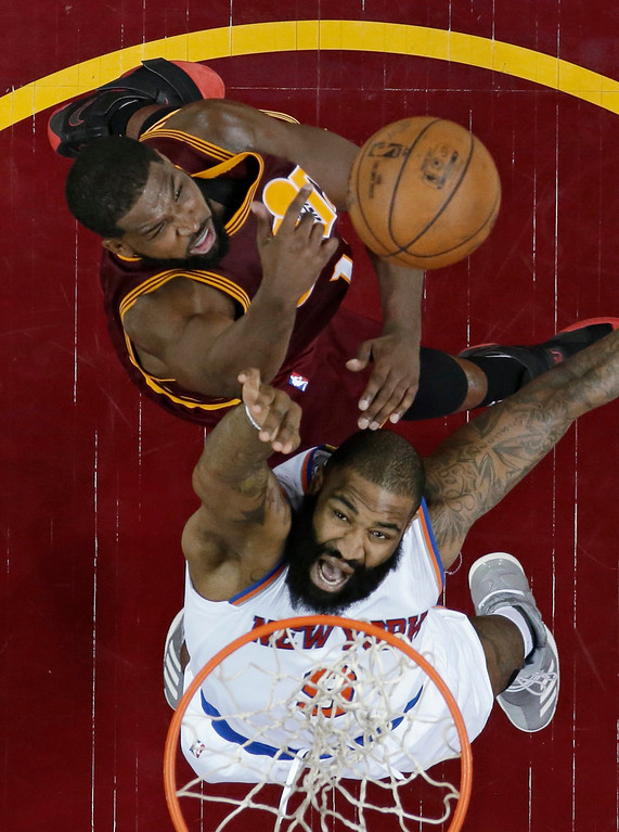 . Cleveland Cavaliers\' Tristan Thompson, top, blocks a shot by New York Knicks\' Kyle O\'Quinn during the second half of an NBA basketball game, Thursday, Feb. 23, 2017, in Cleveland. The Cavaliers won 119-104. (AP Photo/Tony Dejak)