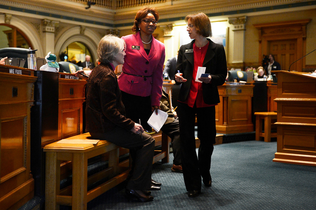 . DENVER, CO. - FEBRUARY 15: Majority Whip Representative Beth McCann, Representative Rhonda Fields and Representative Claire Levy meet in the well of the Colorado House during the debate of four bills that seek to enact universal gun background checks, fees for background checks, limits on magazine size and a ban on conceal carry permits on college campuses at the Denver State Capitol February 15, 2013. Denver, Colorado. (Photo By Joe Amon/The Denver Post)