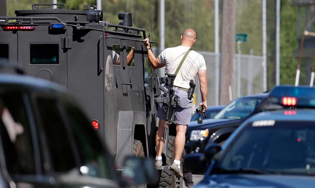 . A Seattle police SWAT team member rides on an emergency vehicle following a shooting on the campus of Seattle Pacific University on Thursday, June 5, 2014, in Seattle. A lone gunman armed with a shotgun opened fire in a building at the small university, killing one person before he was subdued by a student as he tried to reload, police said. Police say the student building monitor disarmed the gunman and several other students held him until police arrived at the Otto Miller building. (AP Photo/Elaine Thompson)