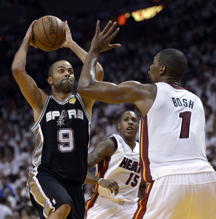 . Chris Bosh (R) of the Miami Heat guards Tony Parker (L) of the San Antonio Spurs during the second  half in Game 2 of the NBA Finals at the American Airlines Arena June 9, 2013 in Miami, Florida.  The Heat won 103-84 to even the best-of-seven championship series 1-1.    BRENDAN SMIALOWSKI/AFP/Getty Images