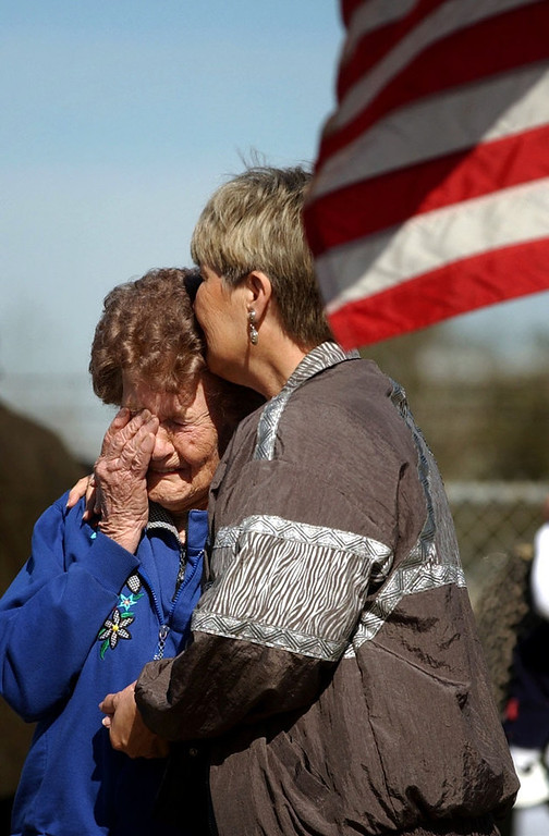 """. Barbara Mikulik  of Houston (right)  kisses her 91-year-old mother Hilda Mikulik of San Angelo, Texas before  the memorial service for space shuttle Columbia astronauts going on with President Bush inside the center on Tuesday, February 4, 2003.  They were outside the gates to the center where flowers, notes, flags are being placed in at a memorial for the astronauts. Barbara brought her mother to the site to witness history and pay a tribute to the \""""courageous men and women who did something for us all.\"""" CYRUS MCCRIMMON, The Denver Post"""