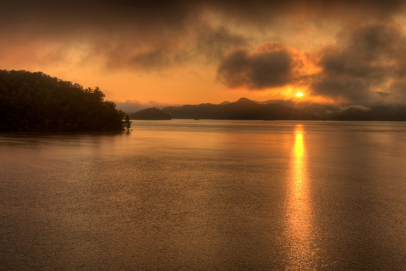 The rising sun peaks over the tops of a mountain range through heavy fog at South Holston Lake in Bristol, TN on Friday, July 25, 2014. Copyright 2014 Jason Barnette