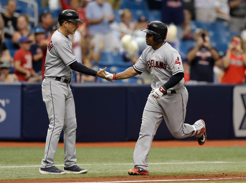 . Cleveland Indians\' Jose Ramirez, right, shakes hands with third base coach Mike Sarbaugh after Ramirez hit a home run off Tampa Bay Rays starting pitcher Blake Snell during the seventh inning of a baseball game Wednesday, Sept. 12, 2018, in St. Petersburg, Fla. (AP Photo/Chris O\'Meara)