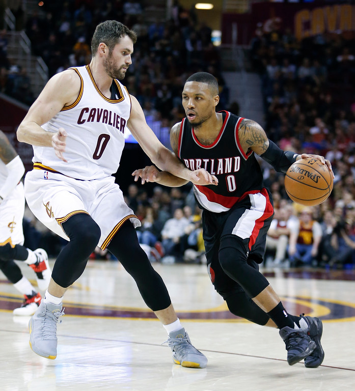 . Portland Trail Blazers\' Damian Lillard (0) drives on Cleveland Cavaliers\' Kevin Love (0) during the second half of an NBA basketball game, Wednesday, Nov. 23, 2016, in Cleveland. The Cavaliers won 137-125. (AP Photo/Ron Schwane)