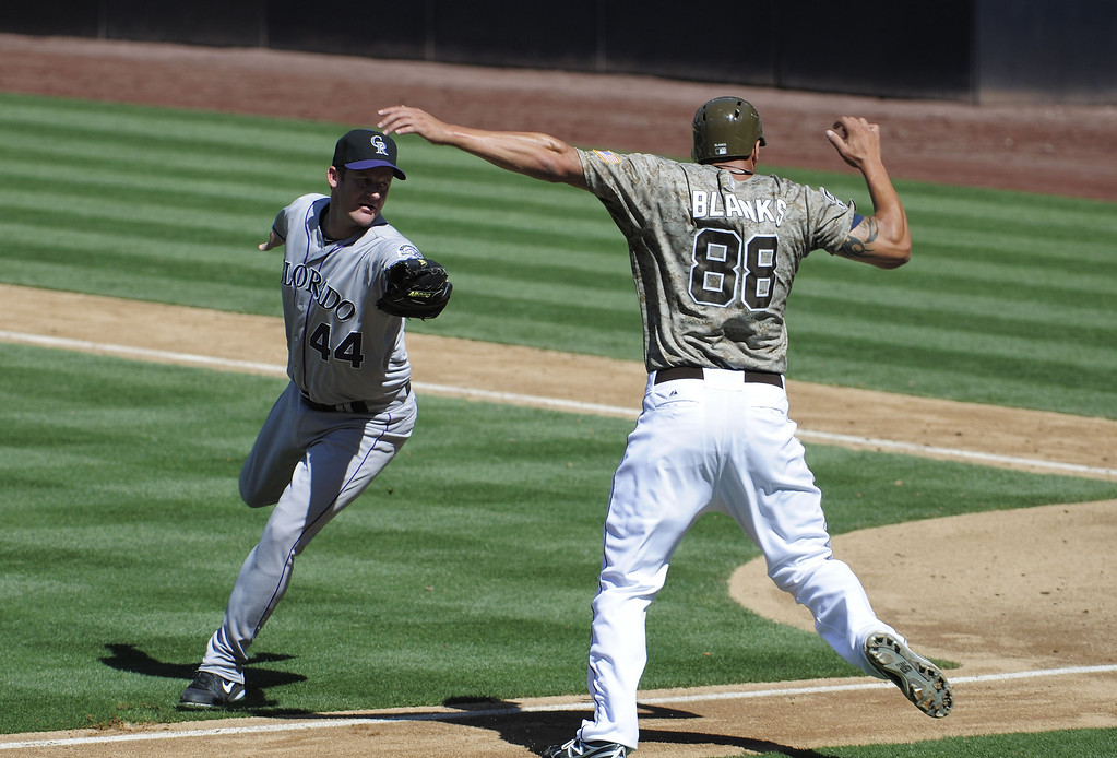 . Kyle Blanks #88 of the San Diego Padres avoids the tag of Roy Oswalt #44 of the Colorado Rockies as he tries to score during the fifth inning of a baseball game at Petco Park on September 8, 2013 in San Diego, California. Blanks was called out after leaving the base path.  (Photo by Denis Poroy/Getty Images)
