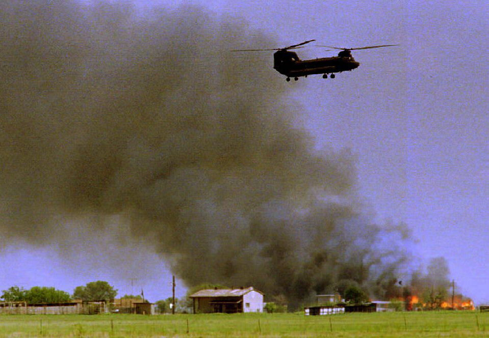 . A National Guard helicopter hovers over the burning Branch Davidian cult compound 19 April 1993 in Waco, TX.     TIM ROBERTS/AFP/Getty Images