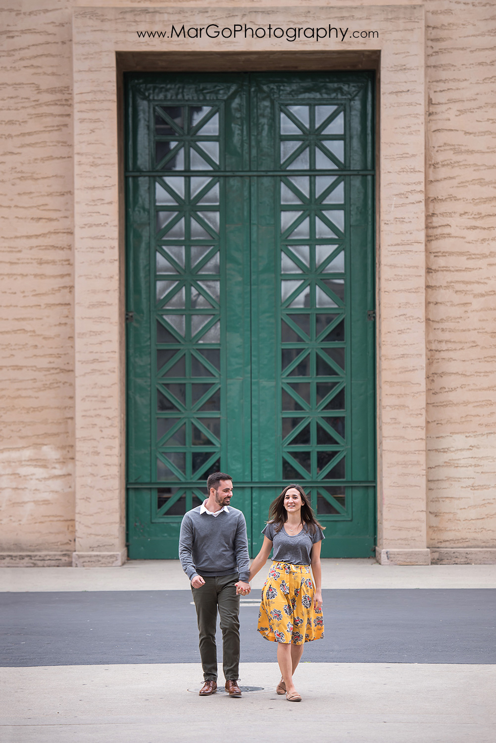 engagement session at Palace of Fine Arts in San Francisco - couple walking in front of green door