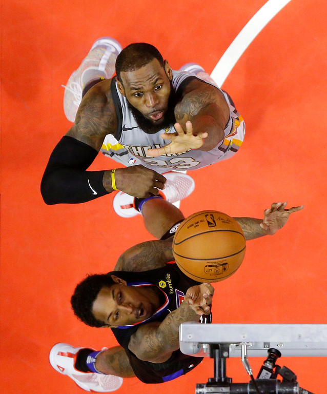 . Los Angeles Clippers guard Lou Williams, below, shoots as Cleveland Cavaliers forward LeBron James defends during the first half of an NBA basketball game, Friday, March 9, 2018, in Los Angeles. (AP Photo/Mark J. Terrill)
