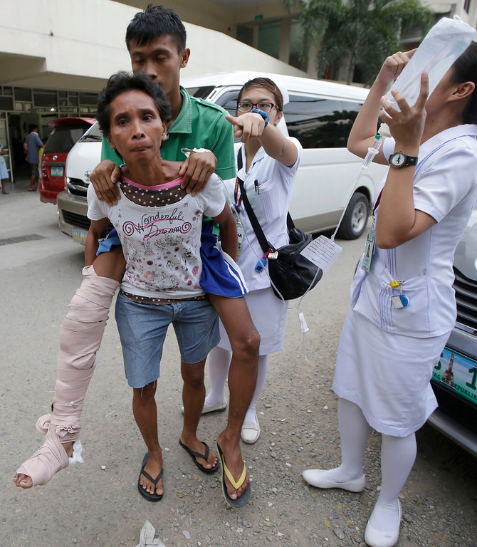 . Nurses assist earthquake victims as they prepare to pitch their beds at the parking lot of a government hospital following a 7.2-magnitude quake that hit Cebu city in central Philippines Tuesday, Oct. 15, 2013.  (AP Photo/Bullit Marquez)
