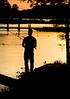 Man fishing on shoreline at dusk during a sunset.