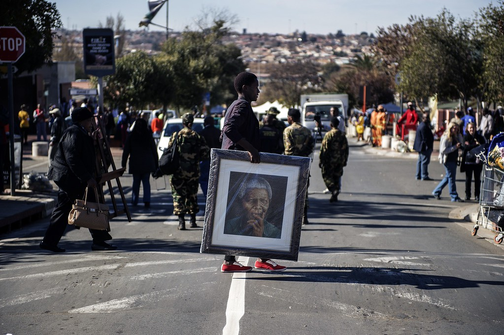 . A woman carries a painting portraying the late Nelson Mandela outisde his former house in Soweto as various activities marking International Mandela Day take place in front of the house turned museum of the late global Icon Nelson Mandela on July 18, 2014 in Johannesburg. Mandela Day is a global call to action that celebrates the idea that each individual has the power to transform the world, the ability to make an impact. Nelson Mandela International Day (or Mandela Day) is an annual international day in honour of Nelson Mandela, celebrated each 18 July (on Mandela\'s birthday). The day was officially declared by the United Nations in November 2009, with the first UN Mandela Day held on 18 July 2010.         (GIANLUIGI GUERCIA/AFP/Getty Images)