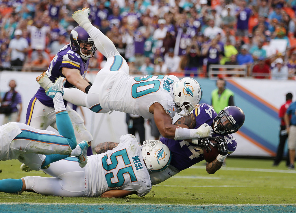 . MIAMI GARDENS, FL - DECEMBER 21:  Running back Matt Asiata #44 of the Minnesota Vikings scores a fourth quarter touchdown as defensive end Olivier Vernon #50 of the Miami Dolphins goes airborne during a game at Sun Life Stadium on December 21, 2014 in Miami Gardens, Florida. The Dolphins won the game 37-35. Photo by Rob Foldy/Getty Images)