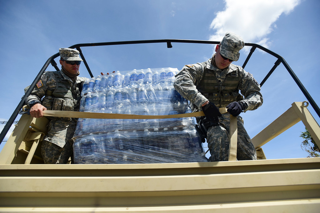 . National Guard Soldiers arrive at Barrio Obrero in Santurce to distribute water and food among those affected by the passage of Hurricane Maria, in San Juan, Puerto Rico, Sunday, Sept. 24, 2017. Federal aid is racing to stem a growing humanitarian crisis in towns left without fresh water, fuel, electricity or phone service by the hurricane. (AP Photo/Carlos Giusti)