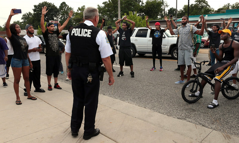 . Protestors blocking Florissant Road raise their hands after being approached by police officers who asked them to stop blocking the street in front of the Ferguson police department on Sunday, Aug. 10, 2014, one day after a Ferguson officer shot and killed Michael Brown. Officers backed down and instead barricaded the street in both directions. (AP Photo/St. Louis Post-Dispatch, Robert Cohen)