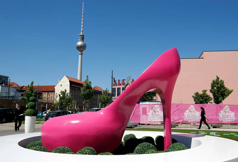""". A giant shoe is pictured outside a life-size \""""Barbie Dreamhouse\"""" of Mattel\'s Barbie dolls in Berlin, May 15, 2013. The life-sized house, covering about 1,400 square metres offers visitors to try on Barbie\'s clothes in her walk-in closet, tour her living room and her kitchen.  REUTERS/Fabrizio Bensch"""