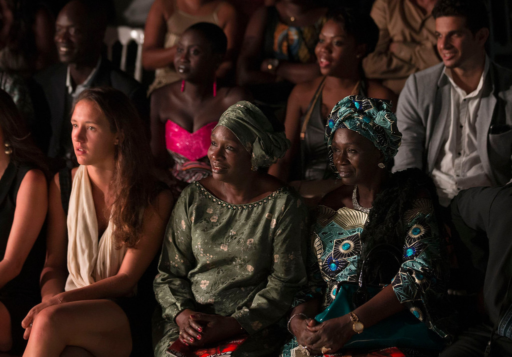 . Spectators watch as models walk the runway, at Hotel des Almadies, in Dakar, Senegal, in the early hours of Sunday, June 23, 2013. After a Friday show held in a dusty marketplace in the working class suburb of Guediawaye, the runway finale of Dakar Fashion Week was held at a luxury hotel and showcased the work of 14 designers from West Africa, Europe, South America, and the Caribbean. (AP Photo/Rebecca Blackwell)