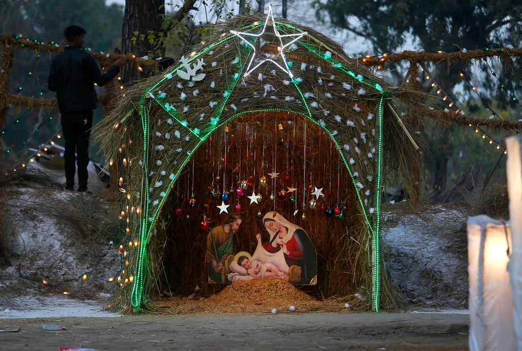 . A Christian boy stands beside a Nativity scene set up in an enclosure specially decorated for Christmas celebrations, at a Christian neighborhood of Islamabad, Pakistan, Sunday, Dec. 24, 2017. (AP Photo/Anjum Naveed)