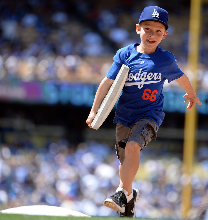 . A young Los Angeles Dodgers fans runs with a base during a Major league baseball game against the San Francisco Giants on Saturday, May10, 2013 in Los Angeles.   (Keith Birmingham/Pasadena Star-News)