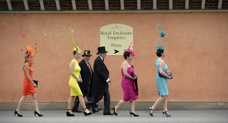 . Racegoers walk along the street as they arrive during the first day of Royal Ascot, in Berkshire, west of London, on June 18, 2013. The five-day meeting is one of the highlights of the horse racing calendar.  Horse racing has been held at the famous Berkshire course since 1711 and tradition is a hallmark of the meeting. Top hats and tails remain compulsory in parts of the course while a daily procession of horse-drawn carriages brings the Queen to the course.  ADRIAN DENNIS/AFP/Getty Images