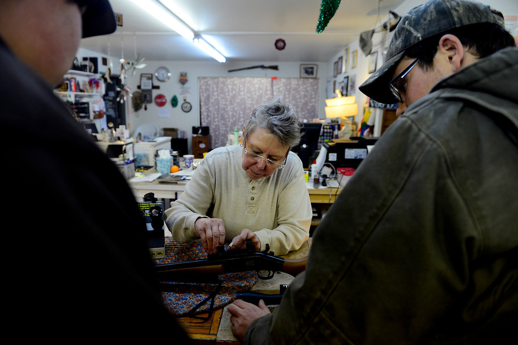 . WALSENBURG, CO - FEBRUARY 26: Howllowpoint Gun Shop Owner Erin Jerant helps mount a scope on a hunting rifle for Justin Noga (right) as friend Ricky Kelly looks on in Walsenburg. Jerant says she has known the two since they were young enough to sit on the store\'s countertops. Gun owners in southern Colorado largely agree that responsible ownership begins at home. (Photo by AAron Ontiveroz/The Denver Post)