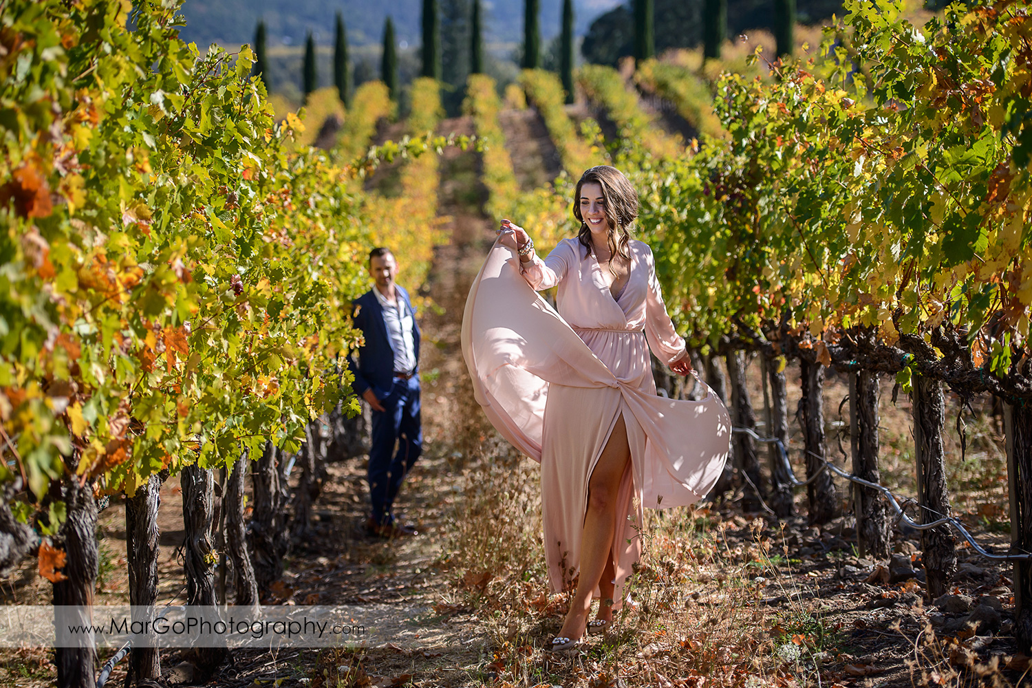 woman in pink dress dancing in the vineyrad with man in blue suit in background during Napa Valley engagement session at Castello di Amorosa in Calistoga