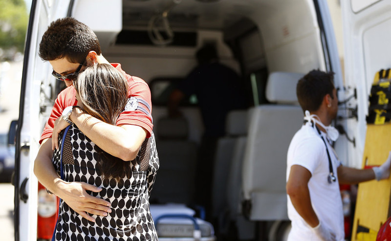 . Relatives of victims embrace next to an ambulance after a fire at a nightclub in Santa Maria, 550 Km from Porto Alegre, southern Brazil on January 27, 2012. The death toll from a fire that tore through a Brazilian nightclub packed with students has risen to 245, an official said Sunday as investigators dug through the charred remains of the building. Felix Zucco/AFP/Getty Images