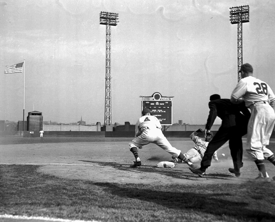 . Jackie Robinson of the Montreal Royals, making his debut in organized baseball in a game with the Jersey City, N.J. team at Jersey City,  April 18, 1946, slides into third base safely the in fifth inning on teammate George Shuba\'s long fly. Larry Miggins waits for the ball. With Robinson connecting for four hits, one of them a three run homer, the Royals took the game 14-1. (AP Photo/John J. Lent, File)