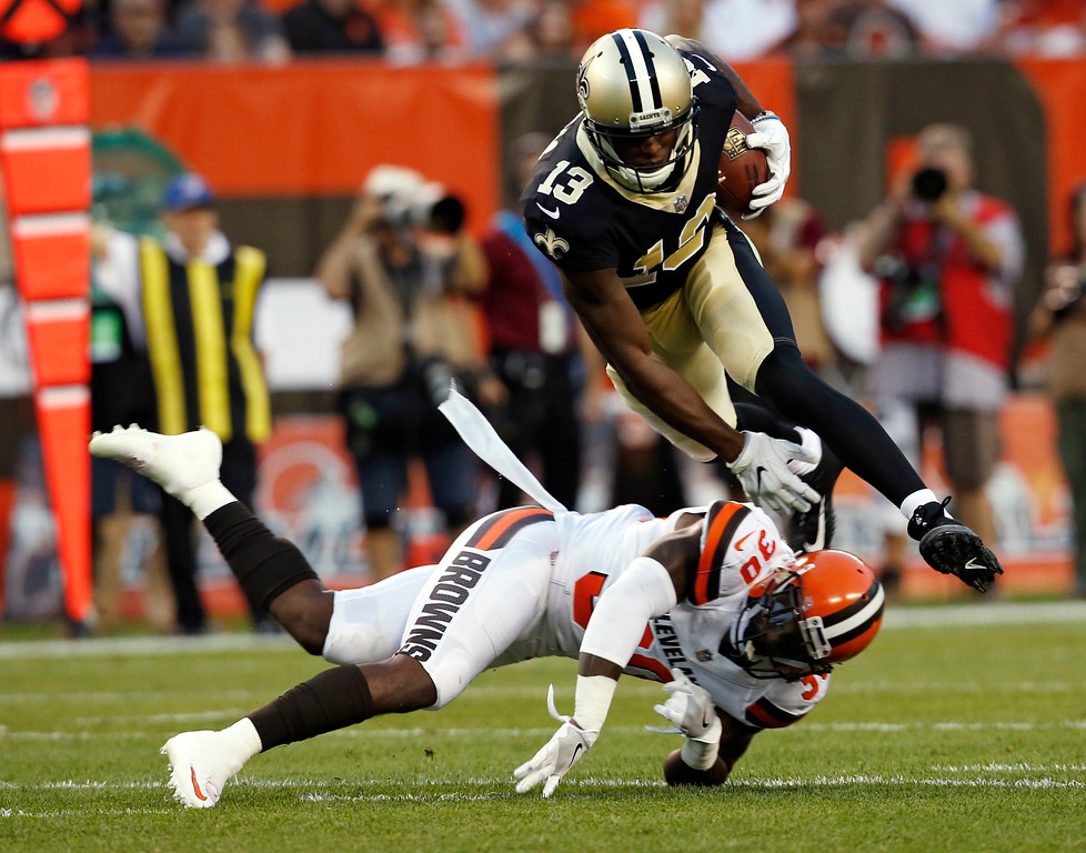 . New Orleans Saints wide receiver Michael Thomas (13) jumps over Cleveland Browns strong safety Derrick Kindred (30) during the first half of an NFL preseason football game, Thursday, Aug. 10, 2017, in Cleveland. (AP Photo/Ron Schwane)